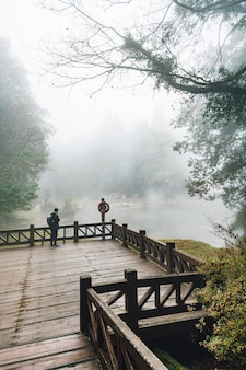Male tourist standing on wooden platform with cedar trees and fog in the forest in alishan.