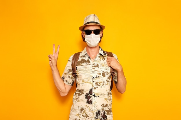Male tourist in sunglasses a medical mask shows a peace sign on a yellow background with his hand