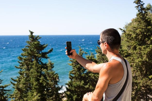 男性観光客が山間部の海の美しい景色をスマホで撮る
