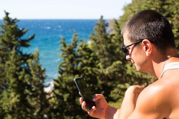 男性観光客が山岳地帯の美しい海の景色をスマートフォンで撮影