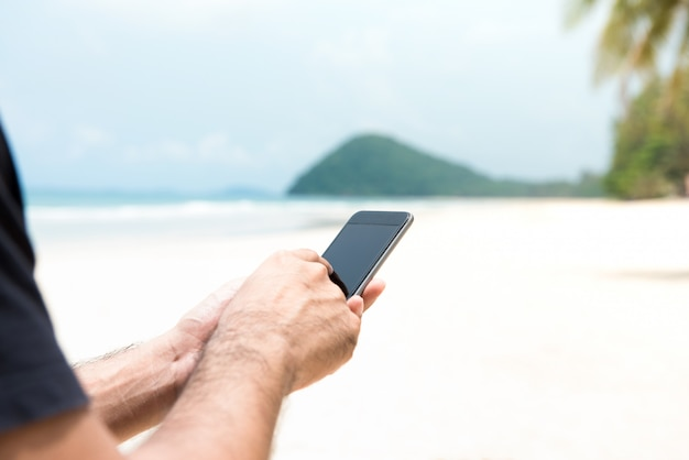 Male tourist using smartphone on the island at the beach in summer vacation