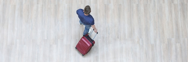 Male tourist walking with suitcase top view