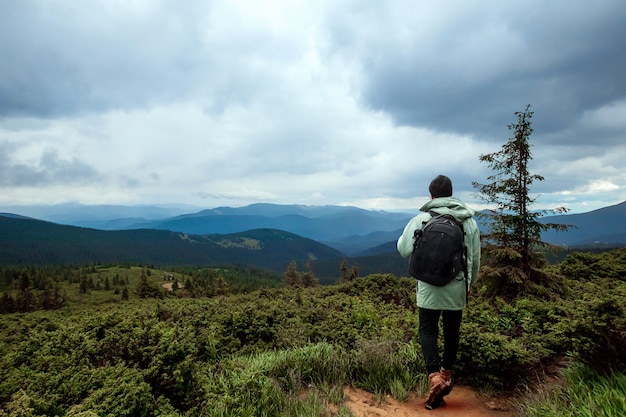 A male tourist walks through a mountainous area with a backpack
