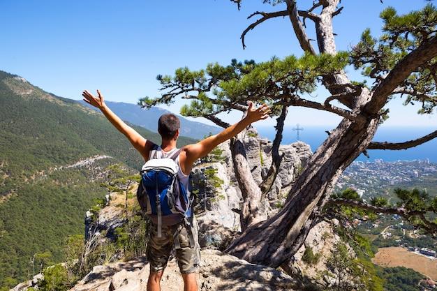 手を上げて山の頂上にバックパックを持った男性観光客は、海岸、街のパノラマを見て、自由に喜んでいます。
