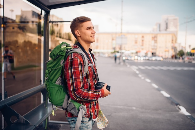 Male tourist with backpack at bus stop. summer travelling, hike adventure over sightseeing, city walking