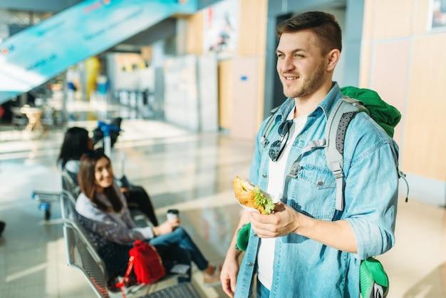 バックパックを持つ男性の観光客はハンバーガー、空港で出発を待っている女性の旅行者を保持しています。