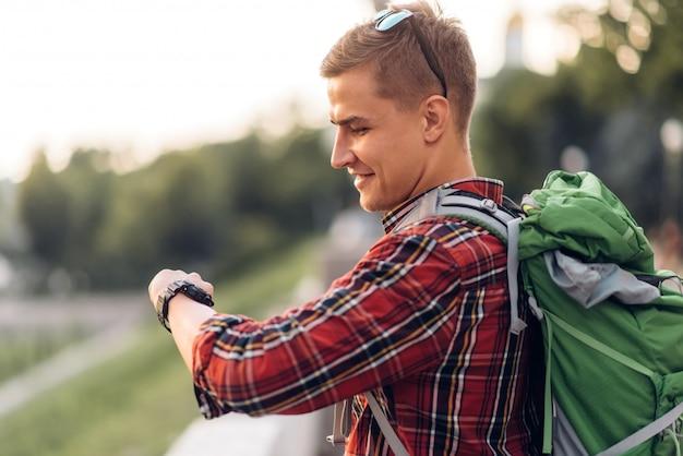 Мужской турист с рюкзаком, глядя на часы, экскурсия по городу. летний поход. поход приключение молодого человека