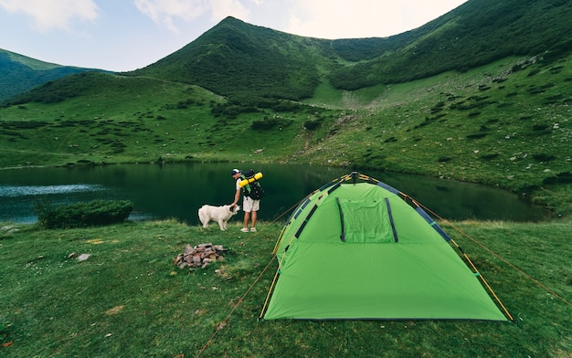 A male tourist with a backpack and a rubber mat stands near a tent by the lake. young hiker with a dog at the foot of the green mountains. travel, vacation, tourism.