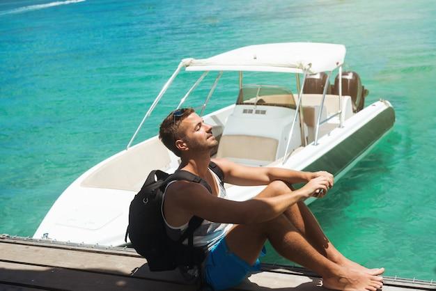 Мужской турист с рюкзаком сидит на пирсе, наслаждаясь приятным солнечным светом