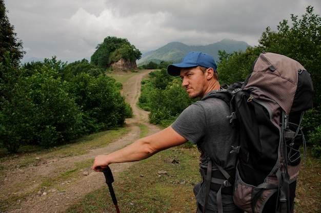 Male tourist with backpack stands near the road