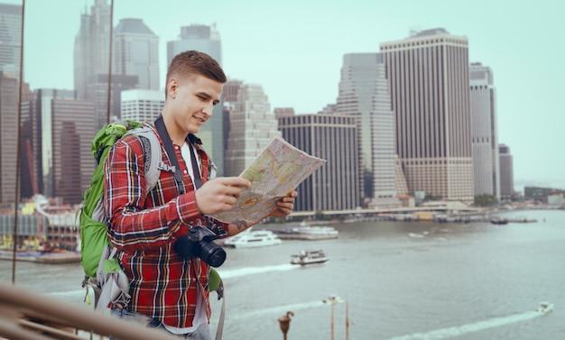 Мужчина-турист с рюкзаком изучает карту городских достопримечательностей, экскурсия по городу. летний поход. поход приключение молодого человека