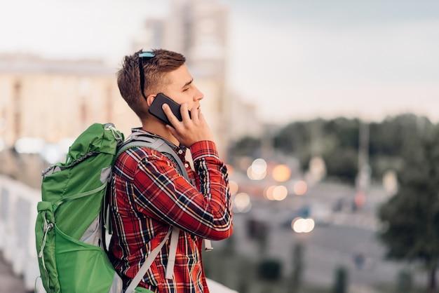 電話で話しているバックパック、町での遠足を持つ男性の観光客。夏のハイキング。若い男のハイキングアドベンチャー