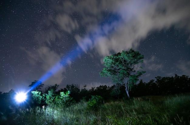 Мужской турист с фонариком на голове, звездное небо в лесу.