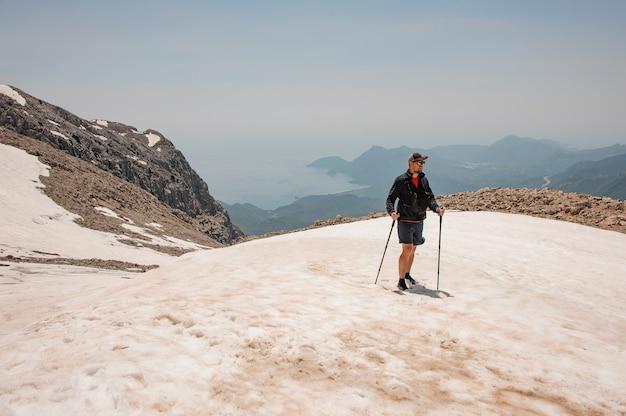 山でのハイキング用具を持つ男性の観光客