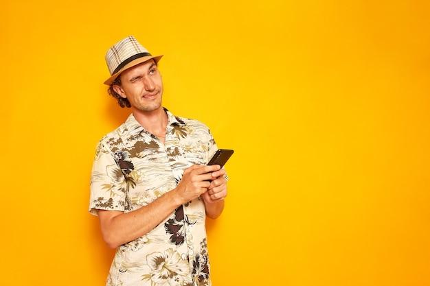 남성 관광객은 문자를 위한 장소가 있는 노란색 배경에 격리된 스마트폰에 메시지를 씁니다.