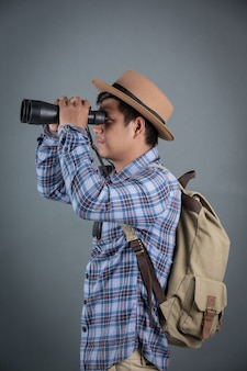 Male tourists backpacking holding binoculars gray background.