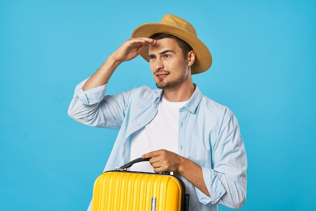 Male tourists in hat with suitcase in hand travel adventure destination blue