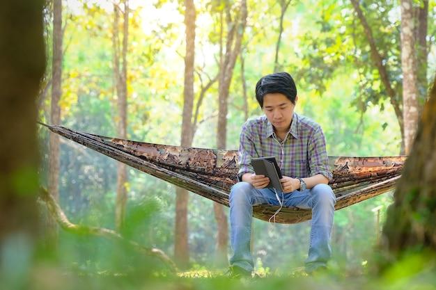 国立公園で音楽を聴いてハンモックで休んでいる男性の観光客