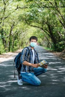 Мужчины-туристы сидят и смотрят на карту на дороге.