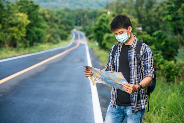 Мужчины-туристы стоят и смотрят на карту на дороге.