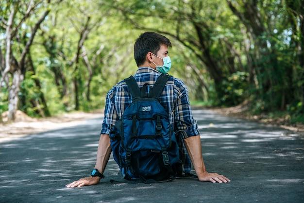 道を歩いてバックパックを運ぶ男性の観光客。
