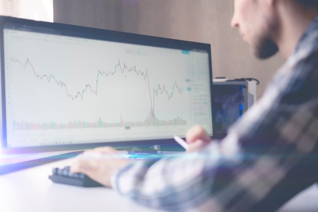 A male trader watching the stock graph on big computer screen at home, chart analysis