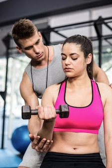 Male trainer assisting woman lifting dumbbell atgym