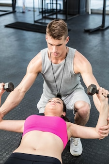 Male trainer assisting woman lifting dumbbell at  gym