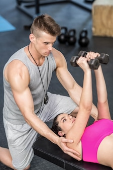 Male trainer assisting woman lifting dumbbells atgym