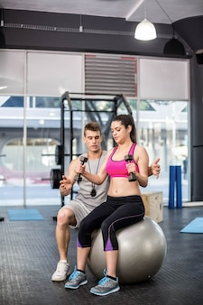 Male trainer assisting woman lifting dumbbells at  gym
