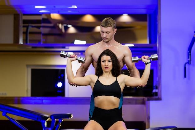 Спортсмен-мужчина-тренер помогает с упражнениями в тренажерном зале спортсменкам, двум людям с гантелями