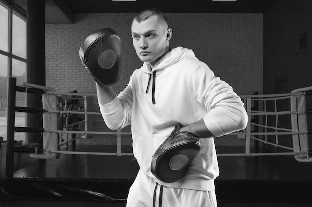 Мужской тренер в тренажерном зале против ринга держит боксерские лапы. концепция смешанных боевых искусств.