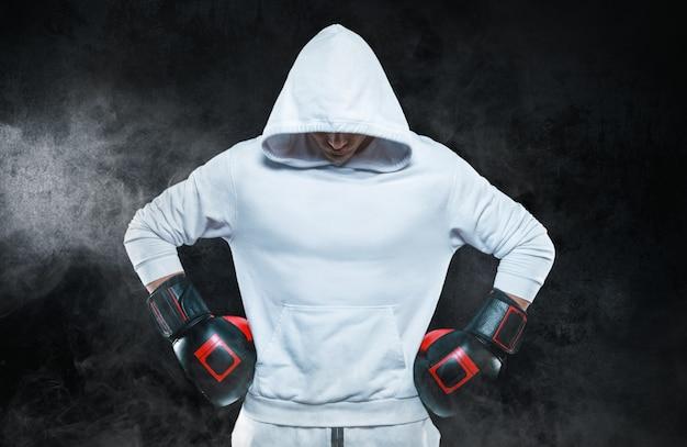 Мужской тренер позирует в студии с боксерскими перчатками. белая толстовка с капюшоном. концепция смешанных боевых искусств.