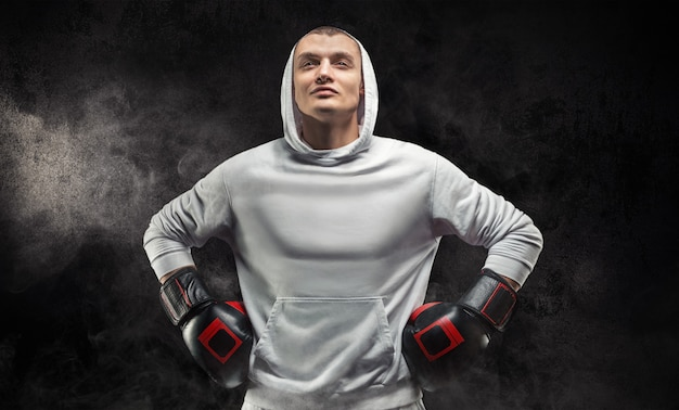 Male trainer posing in the studio with boxing gloves. white hoodie. mixed martial arts concept.