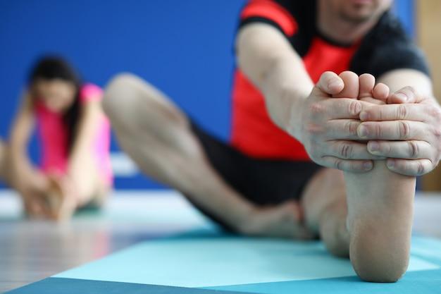 男性トレーナーはストレッチ運動を示しています。