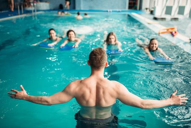 Мужской тренер работает с женской группой на тренировках в бассейне. обучение аквааэробике, водный спорт