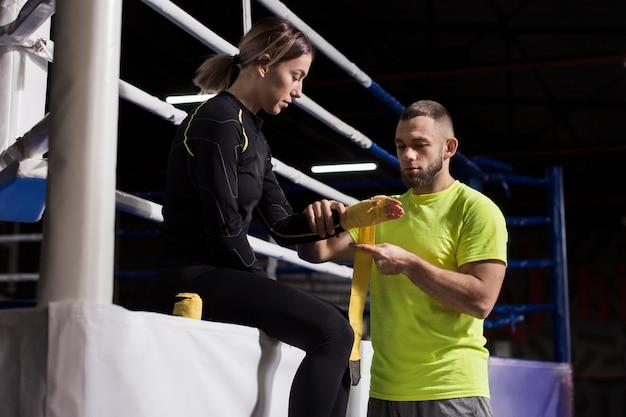 練習の準備で女性のボクサーの手を包む男性トレーナー