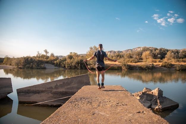 川の横で縄跳びをする男性のトレーニング