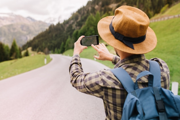 Male traveler in brown hat searching right road by using online map standing on beautiful mountain