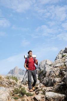 배낭에 자신의 필수품을 가지고 산에서 하이킹하는 남성 여행자