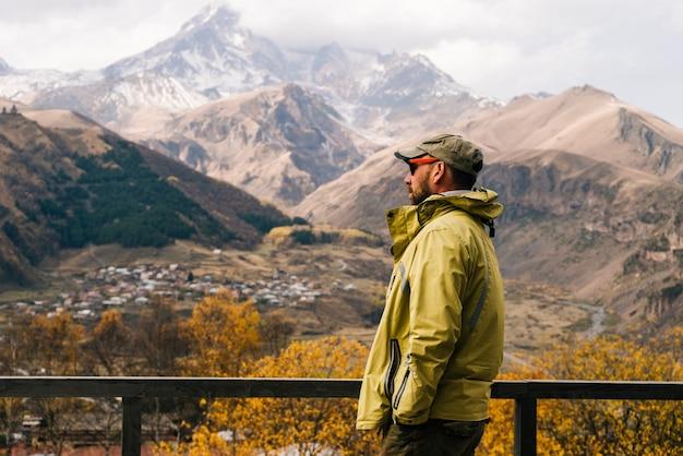 ジャケットとメガネをかけた男性旅行者は、山の自然ときれいな空気を楽しんでいます