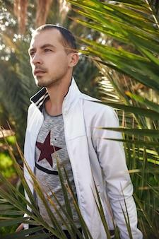 Мужчина-путешественник в портрете оазиса тропических лесов на фоне листьев пальм, небритый парень среди тропической растительности. оазис в пустыне марокко. откройте для себя неизведанное в джунглях