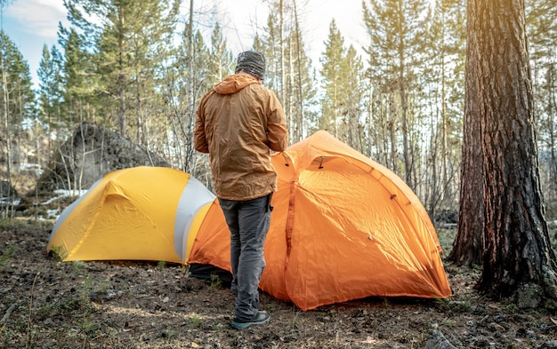 A male traveler is standing in the forest near the tents in a tent camp. concept of hiking, spending time in nature.