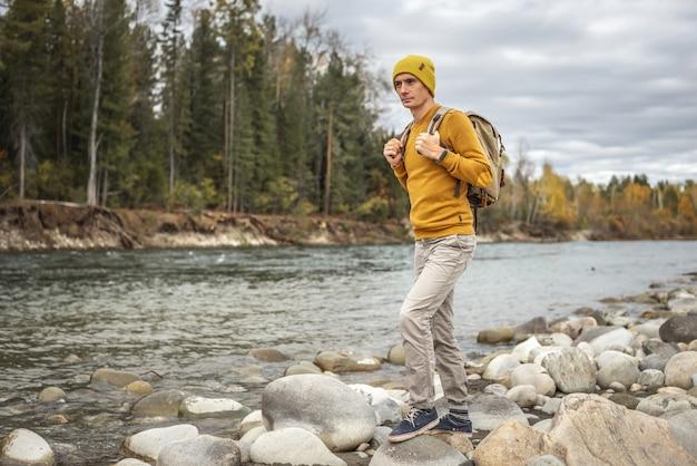 남성 여행자가 가을 숲을 배경으로 해안에 거대한 돌이 있는 빠른 산 강을 따라 걷고 있습니다. 하이킹과 여행의 개념