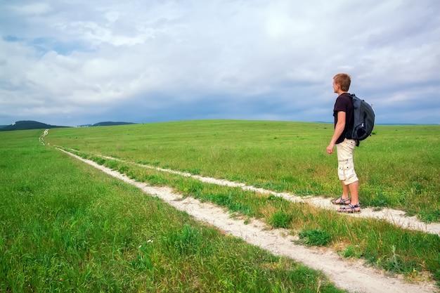 Путешественник-мужчина идет по полю на фоне гор