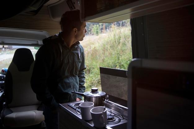 Male traveler making his coffee in a van