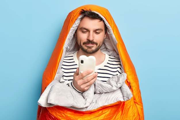 Male traveler poses in orange warm sleeping bag, spends leisure time near sea, concentrated in smartphone, finds right destination poses indoor