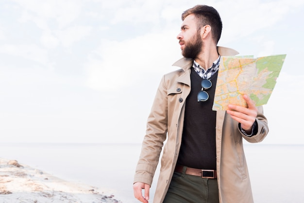 Male traveler standing on beach holding map in hand looking away