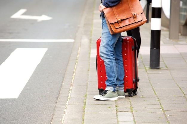 Male traveler standing by the street with suitcase