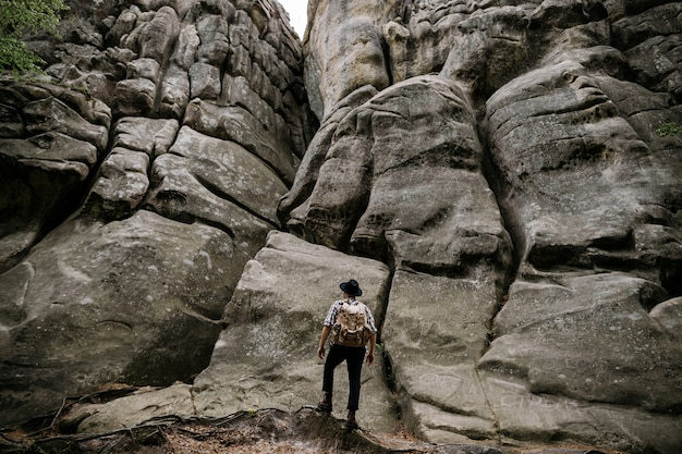 A male traveler stands with a backpack in front of a large rock in the mountains